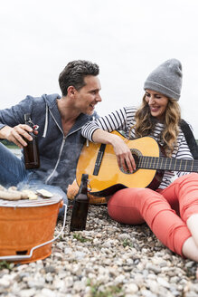 Happy couple with beer bottles, guitar and grill relaxing on pebble beach - UUF14505