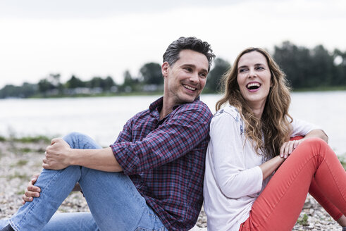 Happy couple sitting at the riverside - UUF14526