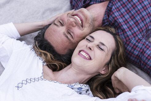 Happy affectionate couple lying on a blanket - UUF14529