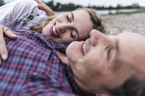 Affectionate happy couple lying outdoors - UUF14538