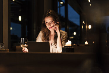 Woman having glass of white wine looking at laptop - UUF14544