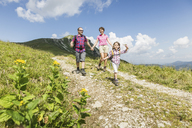Parents and daughter walking on dirt track, Tyrol, Austria - CUF40412
