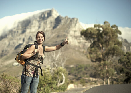 Young woman hitchhiking from Table Mountain, Cape Town, South Africa - CUF40481
