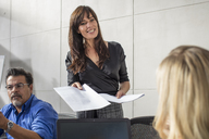 Smiling businesswoman handing over paper on a meeting in conference room - ZEF15809