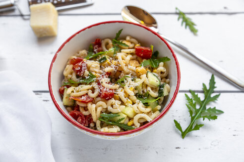 Bowl of noodle salad with corn, cucumber, tomatoes, rocket and grated parmesan - SARF03825