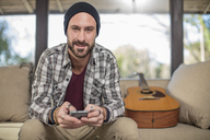 Portrait of smiling young man at home sitting on couch with guitar using cell phone - ZEF15815