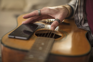 Close-up of man's hand, cell phone and guitar - ZEF15818