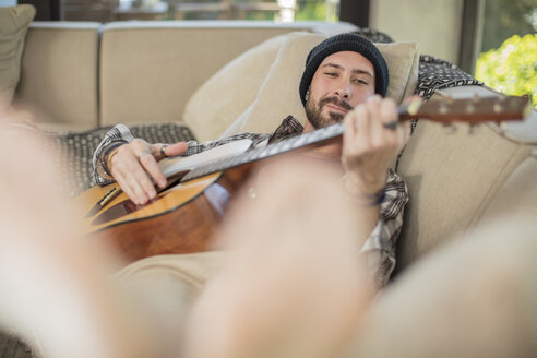 Young man at home lying on couch playing guitar - ZEF15827