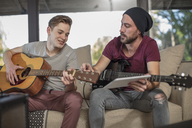 Musician teaching student how to play guitar - ZEF15833