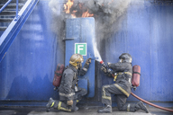 Firefighters tackling flames behind steel door in fire simulation training facility - CUF40679