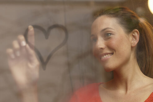 Smiling woman drawing on window - CUF40733