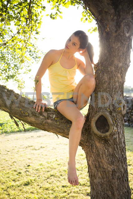 Serious girl sitting on tree in summer - LVF07253