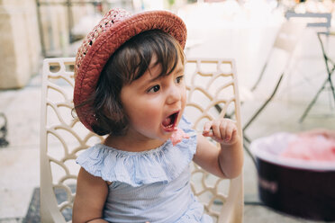 Cute toddler girl eating an ice cream on a terrace - GEMF02112
