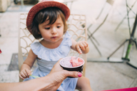 Cute toddler girl eating an ice cream held by her mother - GEMF02115