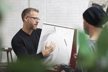 Artist discussing drawing with man in studio - ZEF15874