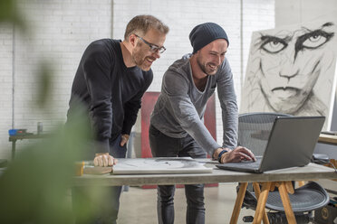 Smiling artist using laptop with man in studio - ZEF15877