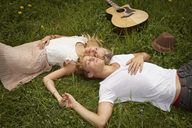 Young couple lying on grass with eyes closed - CUF41191