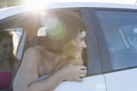 Woman looking over shoulder through car window - CUF41254