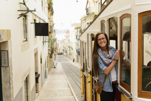 Portrait of young female tourist riding tram in Lisbon, Portugal - CUF41326