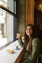 Young female eating sandwich in Barcelona cafe, Spain - CUF41332