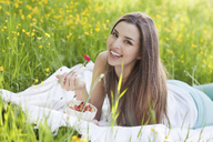 Young woman in field of buttercups eating strawberries - CUF41359