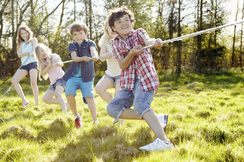 Group of young children playing tug o war - CUF41392