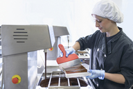 Chocolatier filling chocolate moulds in chocolate factory - CUF41434