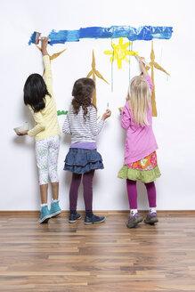 Three girls painting wind turbines on wall - CUF41470
