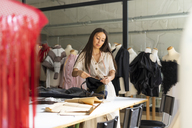 Young fashion designer working in her studio - AFVF00750