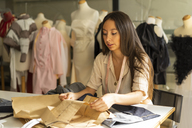 Young fashion designer working in her studio - AFVF00753