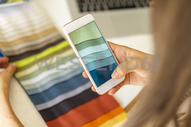 Fashion designer taking pictures of fabric samples with ger mobile phone - AFVF00762