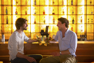 Two men sitting at bar with bottles of beer - CUF41501
