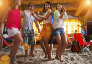 Friends dancing on sand at indoor beach bar - CUF41510