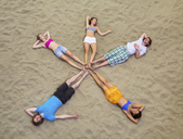 Aerial view of friends lying in star shape on sand - CUF41528