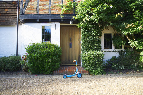 Toy scooter parked outside cottage - CUF41761