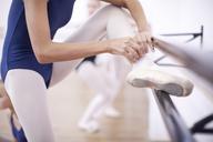 Ballerina fastening ballet slipper at the barre - CUF41893