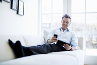 Man relaxing on sofa using digital tablet and smartphone - CUF41971