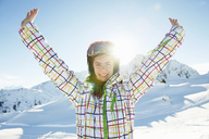 Portrait of teenage girl skier with arms outstretched, Les Arcs, Haute-Savoie, France - CUF42172