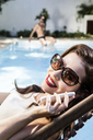 Young woman wearing sunglasses on cell phone - CUF42304
