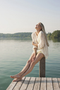 Young woman sitting on pier post - CUF42349