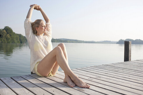Young woman relaxing on lake pier - CUF42352