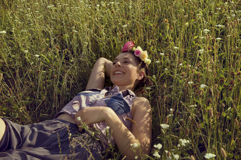 Young woman lying in meadow with flowers in her hair - CUF42355