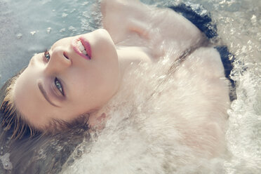 Close up portrait of young woman lying back in sea - CUF42358