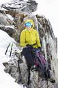 Woman in climbing gear resting on mountain - CUF42385