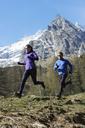 Mid adult couple running, Chamonix, France - CUF42415