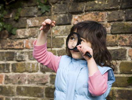 Girl looking at worm with magnifying glass - CUF42451