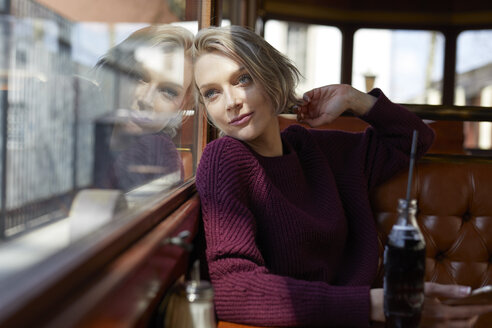 Portrait of blond woman in a cafe looking out of window - PNEF00720
