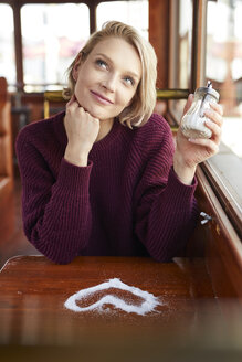 Portrait of smiling blond woman with heart-shaped sugar on table - PNEF00723