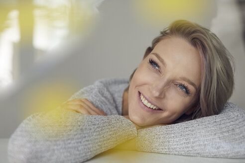 Portrait of happy blond woman leaning on table - PNEF00735