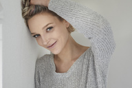 Portrait of smiling blond woman wearing grey pullover - PNEF00738